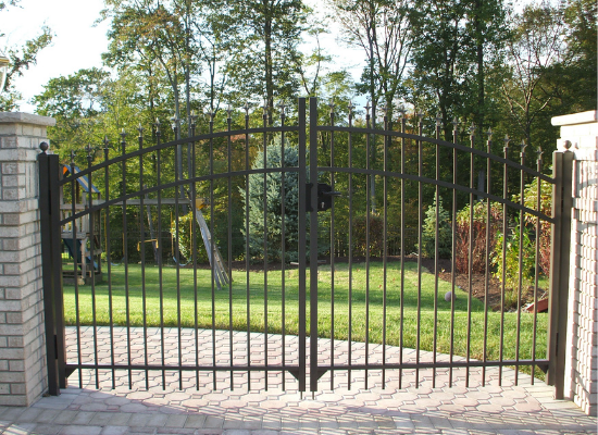 Black aluminum double arch gate in a driveway with stone pillars