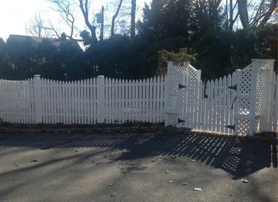 White scalloped vinyl fence and gate with lattice installed by Artistic Fence