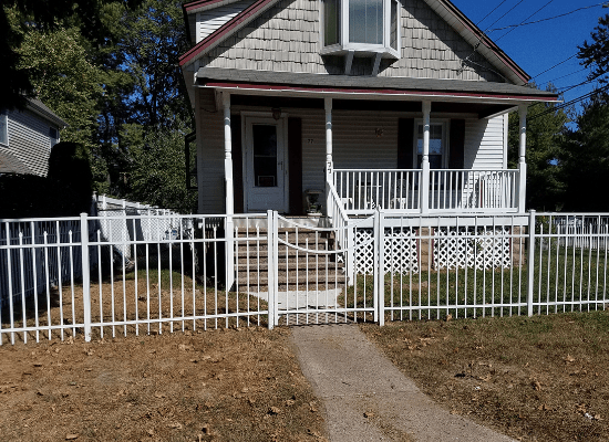 White aluminum fence in a front of a house with a single gate