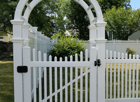 White vinyl picket fence, scalloped single gate, and arbor at a home installed by Artistic Fence