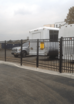 Black aluminum fence installed at a commercial property by the good fence people at Artistic fEnce. A black fence with a double gate