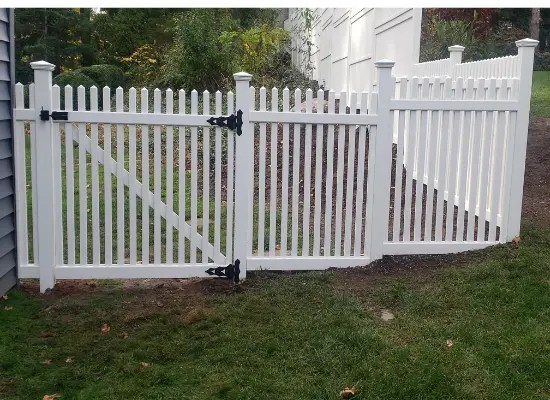 White vinyl picket fence and gate with black latches installed at a residential property in New Jersey by Artistic Fence