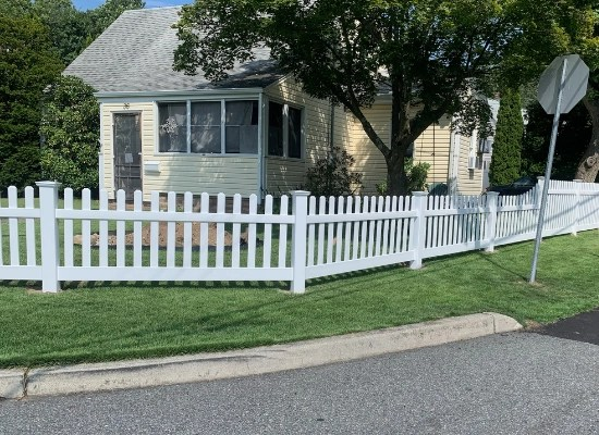 White fence outside of a yellow home in Haskell, New Jersey installed by Artistic Fence