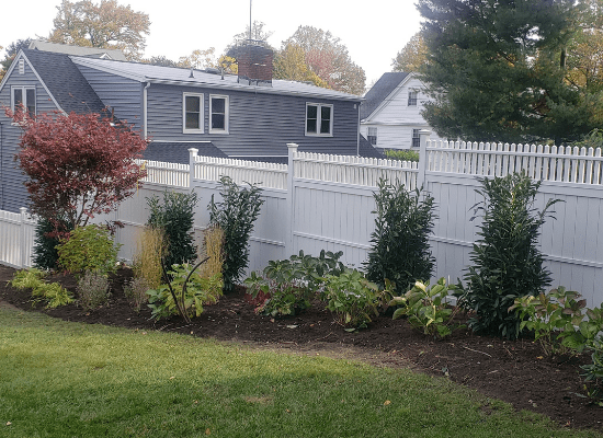 White wood open topped privacy fence stepped with a hill in the homeowners backyard, installed by Artistic Fence Company in New Jersey