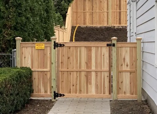 Solid wood fence with gate and midrail