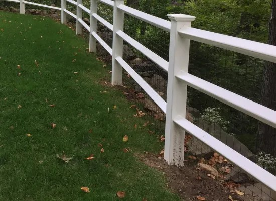White post and rail fence with welded wire mesh in between the rails
