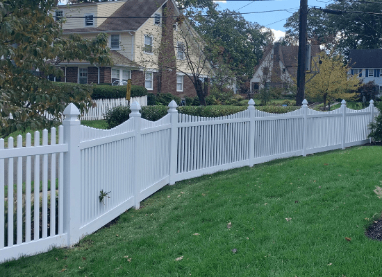 White vinyl scalloped top picket fence in a yard