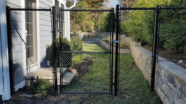 Black chain link tall fence and gate with latch at a residential property