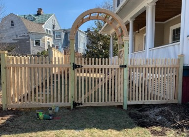Picket wood fence with gate and arbor designed by Artistic Fence