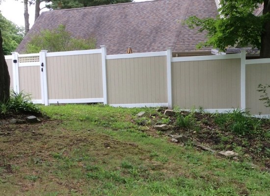 Tan and white stepped privacy fence with narrow walk gate with square lattice top
