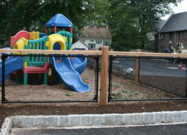 Custom black chain link fence with wood posts at a playground