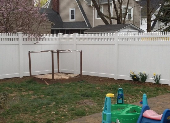 Backyard fence made of vinyl in suburban style with open top