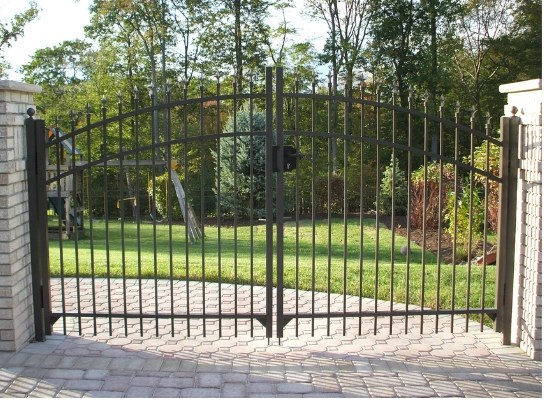 Black aluminum double driveway gate with stonework posts