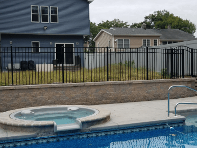 Aluminum pool fence at a residential property surrounding a pool and hot tub