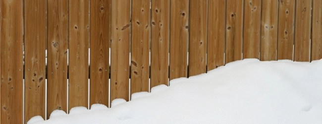 snow piled up on a wood plank fence
