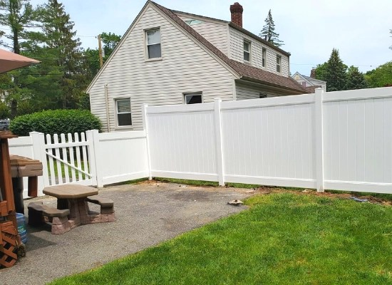 White pvc fence installed by Artistic Fence in Wayne, NJ | Solid white pvc fence with deco rail and bar harbor picket fence gate