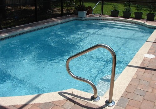 An inground pool with stairs and a railing