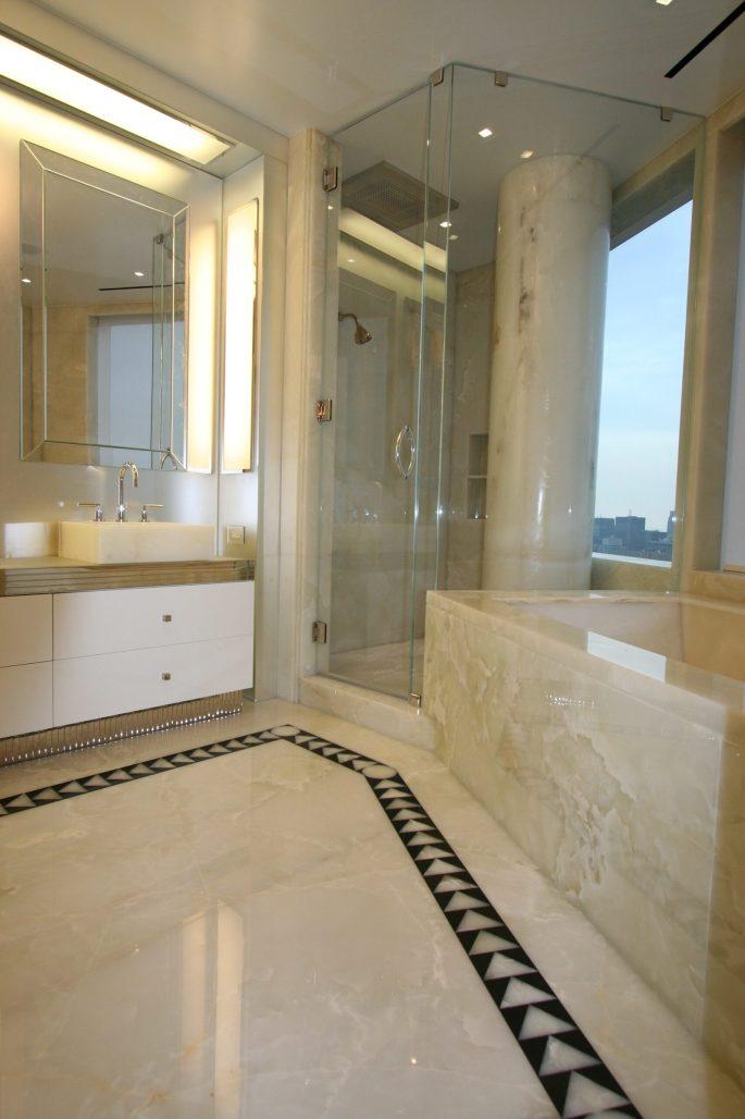 Master bathroom with white onyx floor, walls, sinks, bathtub and column