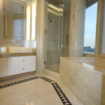 Master bathroom with white onyx floor, walls, sinks, bathtub and column