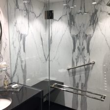 Master bathroom shower in bookmatched calacatta marble slab walls