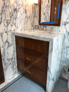 His bathroom vanity and walls in arabescato calacatta marble