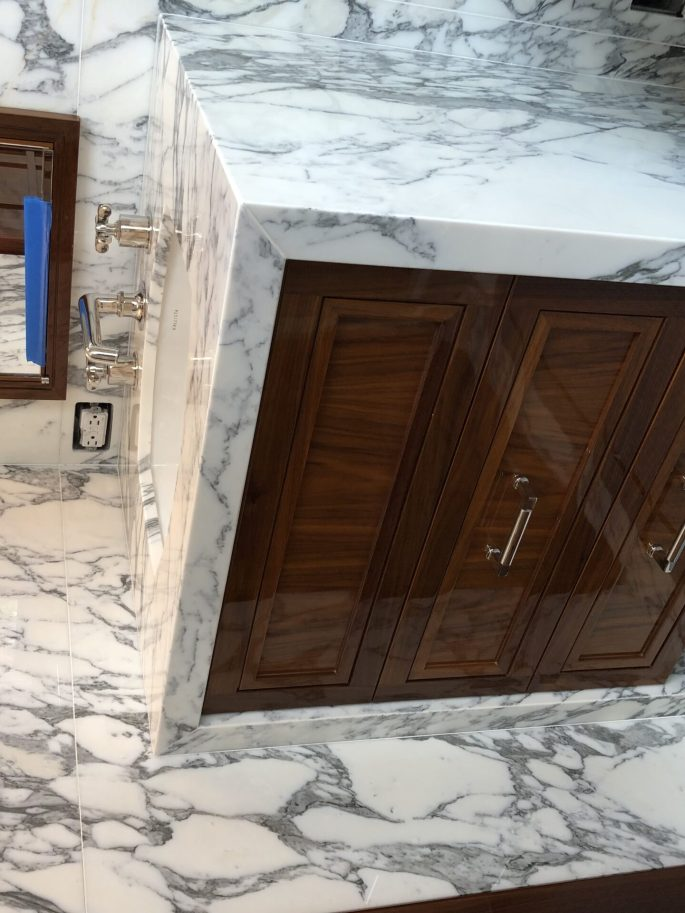 His bathroom vanity and walls in arabescato calacatta marble