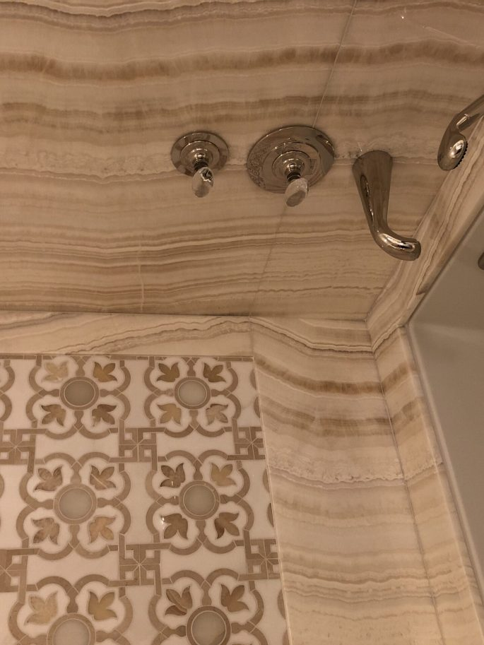 Her Bathroom bathtub top and walls in Ivory onyx slab and custom mosaic