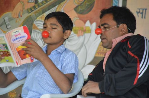 School teacher Tariq Malik clowning with student in Jainabad village school Gujarat