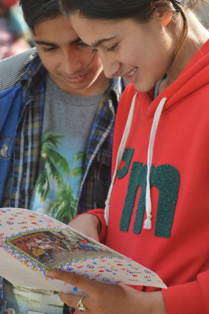 a young volunteer reads the letters with a student