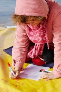 Artist Elisa Vladilo writing on her tarpaulin work 'Rhyme of Origin'