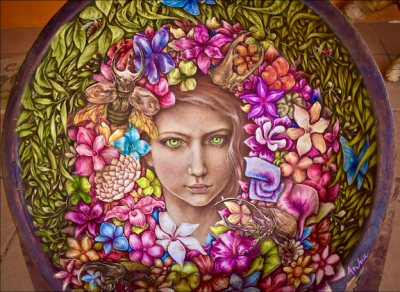 Oil painting of woman with flowers and foliage within a wooden bowl