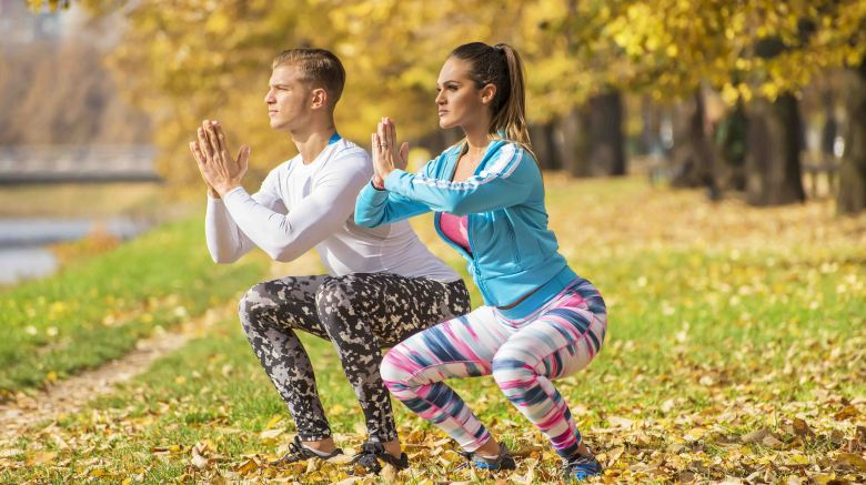 Beautiful young couple doing squats together in the park. Autumn