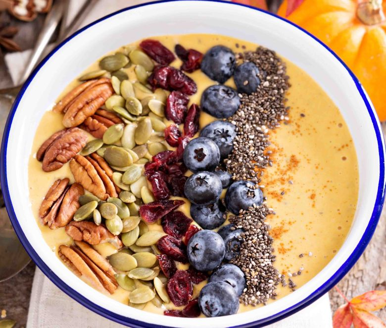 Pumpkin smoothie bowl with chia seeds, pecans, cranberries