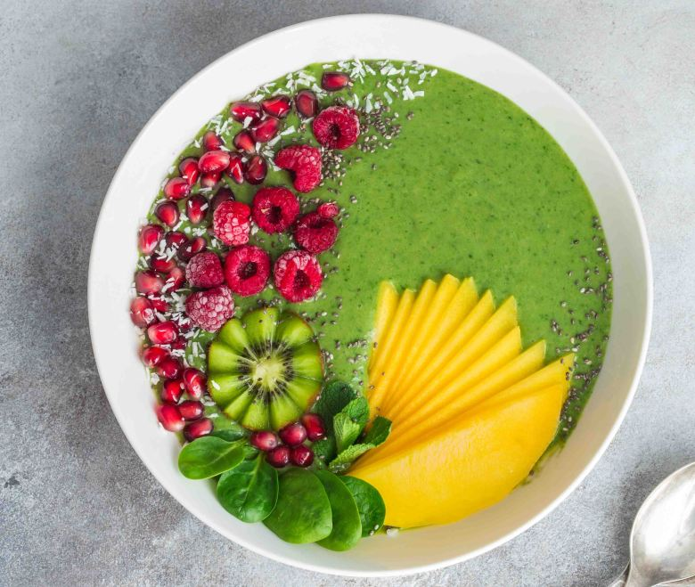 green smoothie bowl with spinach, mango, kiwi and raspberry. Hea