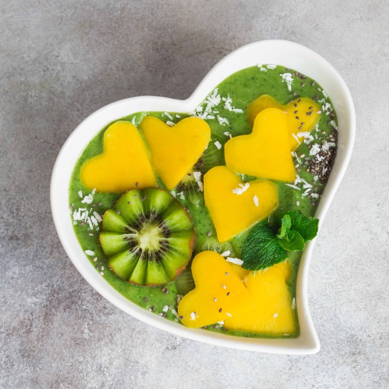 fresh green spinach smoothie bowl with  mango and  kiwi