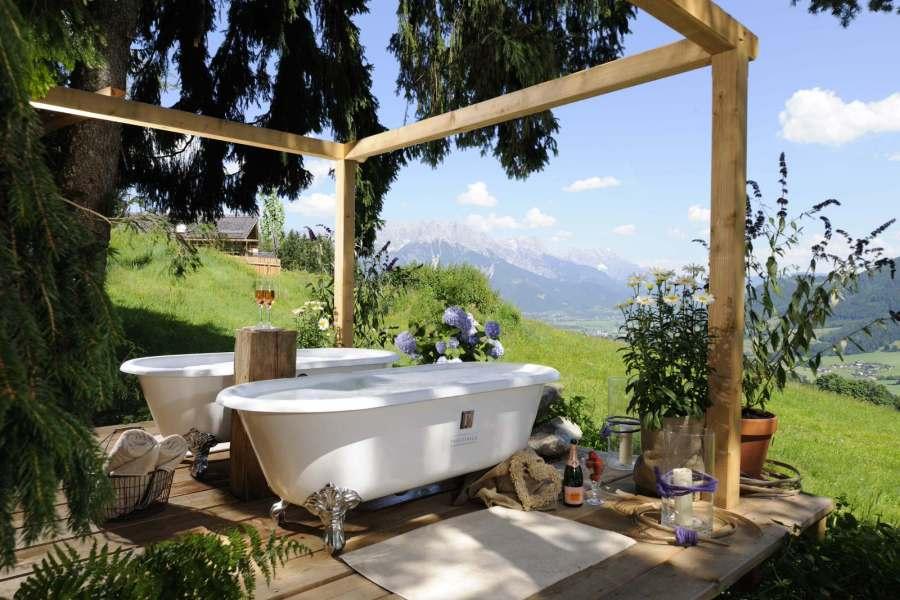 Relaxen im Waldbad: Zwei Badewannen, die mit frischem, warmen Quellwasser und wohltuenden Essenzen gefüllt sind.