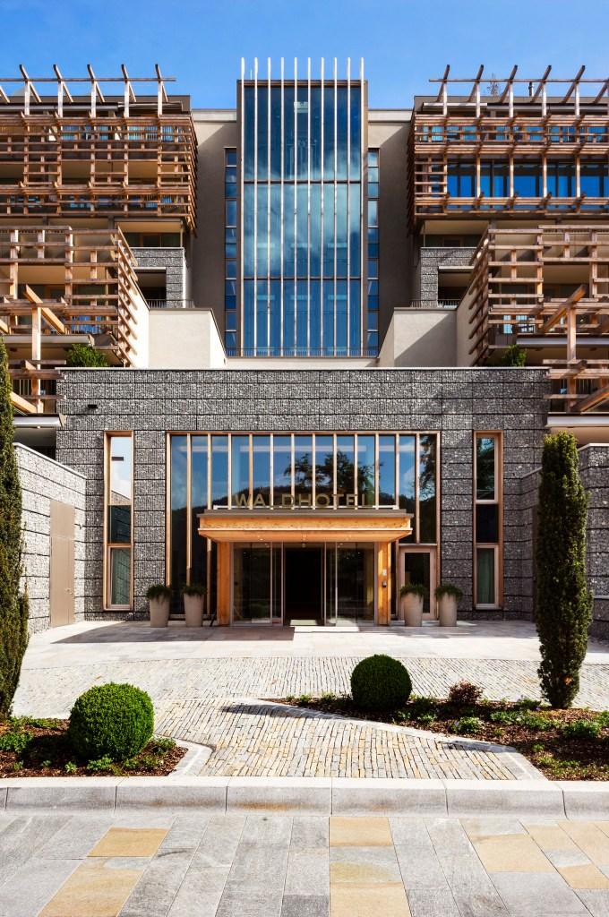 WALDHOTEL HEALTH & MEDICAL EXCELLENCE: Inspiriert von der Walser-Architektur und der alpinen Bautradition sind die Fassaden mit Gabionen gestaltet, die mit dem Gestein aus dem Aushub des Berges gefüllt sind - sie setzen die Stützmauern des Hanges fort.