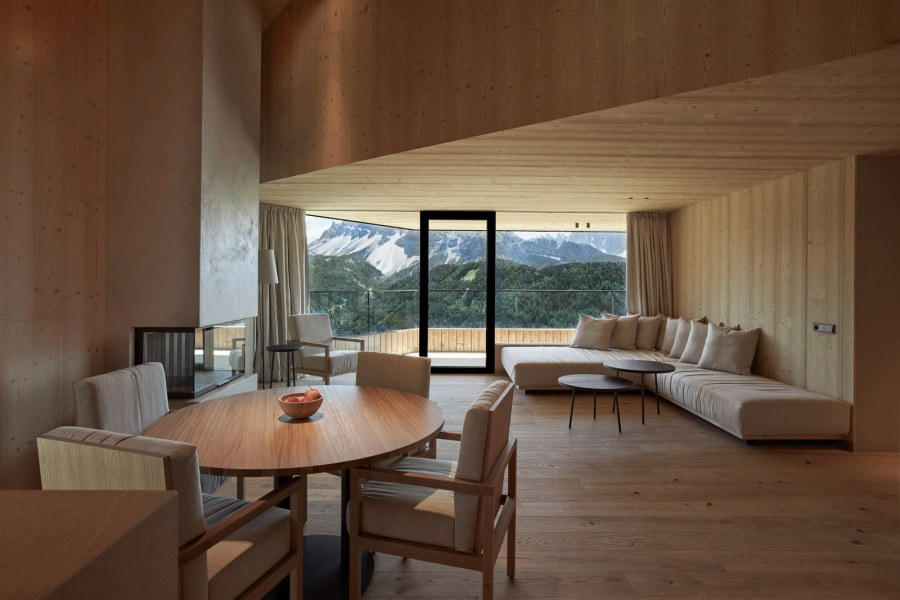 Penthouse Suite: Der großzügige Wohnbereich ist mit Sitzgelegenheit und TV, einer Bar, einem großen Esstisch, einem Gäste-WC und offenem Kamin ausgestattet. Nach Süden hin öffnet sich eine große Terrasse mit Tisch und Sitzgelegenheit.