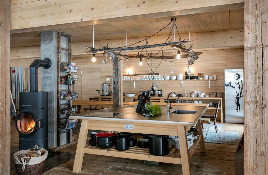 Endlich gemeinsam Kochen zu Ende gedacht. Im Zentrum des Mesnerhof-CAMP ruht der quadratische Küchentisch, maßgefertigt, 4 m² Arbeitfsfläche von allen Seiten nutzbar.
