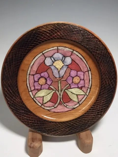 A cherry plate with textured embellishments and colored center, woodturning design