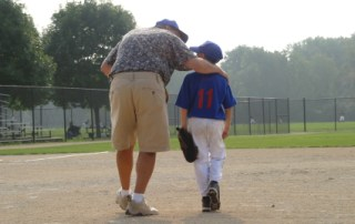 Father offering coaching to his young baseball player son