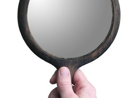 image of a hand holding a mirror