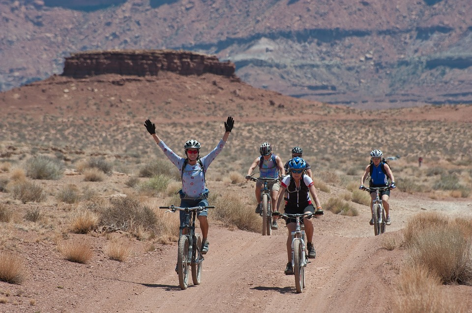 Group riding bicycles through the desert. Rider with hands upraised in joy.
