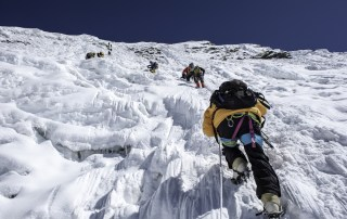 Climbers scaling a vertical face of Ice in Nepal