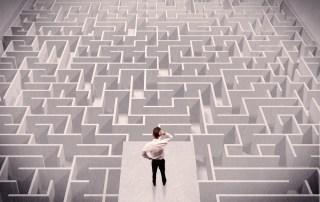 businessman staring at a complex maze