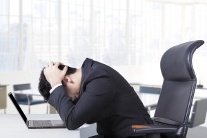 businessman with his head on desk in frustration
