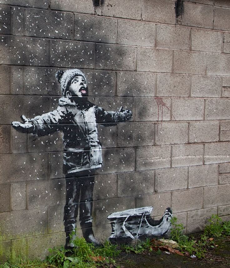 "Banksy. A boy enjoys ""snow"" flakes."