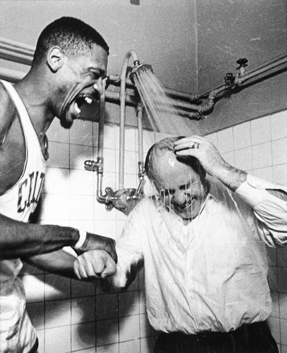 Black and white photograph of Celtics' great Bill Russell and his coach Red Auerbach in the showers celebrating a victory.