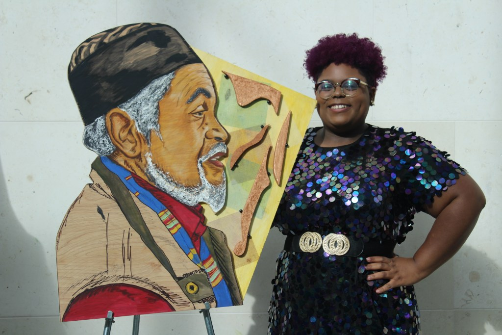 Photograph of artist Chanel Thervil with her artwork.