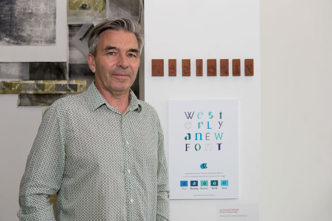 BA Hons Graphic Design graduate Alan Qualtrough with his work at the BOSS exhibition